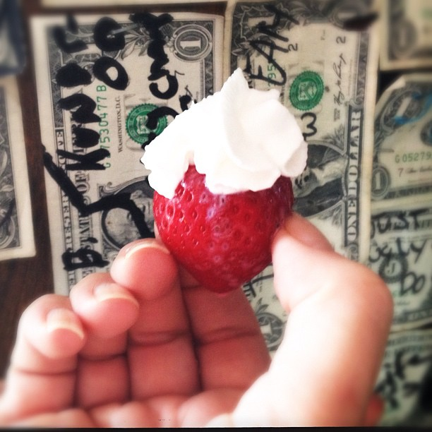 A strawberry infused with alcohol and topped with whip cream.