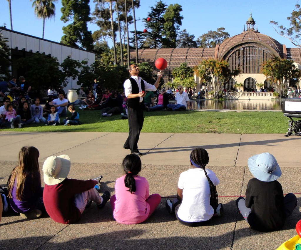 Kids watching a performer at the park. The botanical building and reflecting pool is in the background.