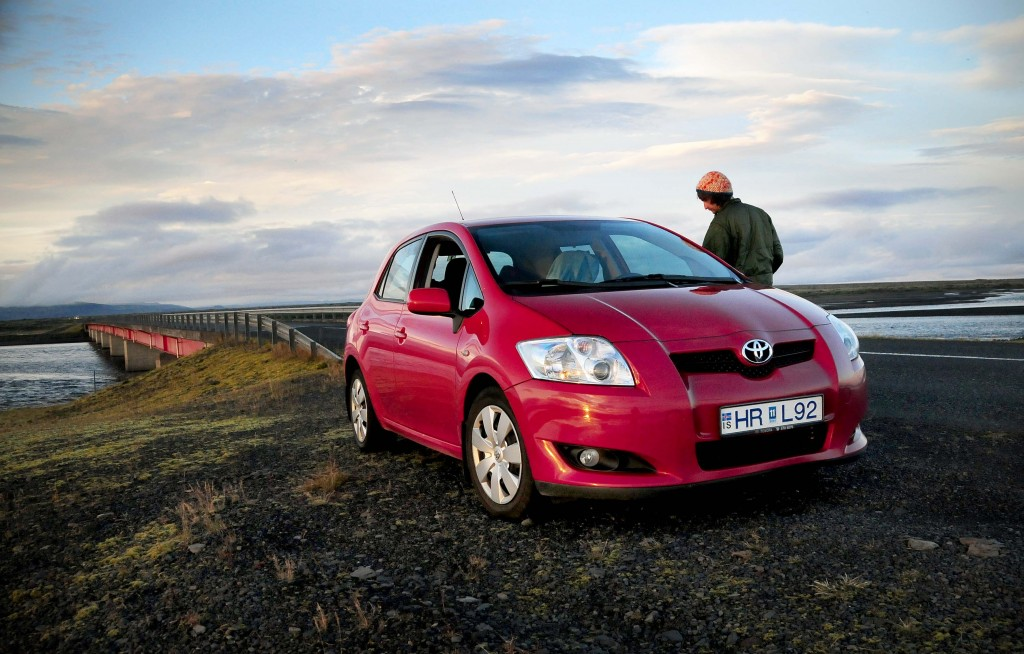 A man looks at his car on the Ring Road and thinks about Iceland car rental tips for a travel story.