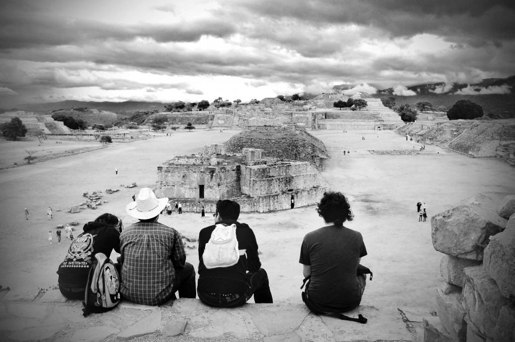 Four travelers looking out over the ruins of Monte Alban in Oaxaca, Mexico.