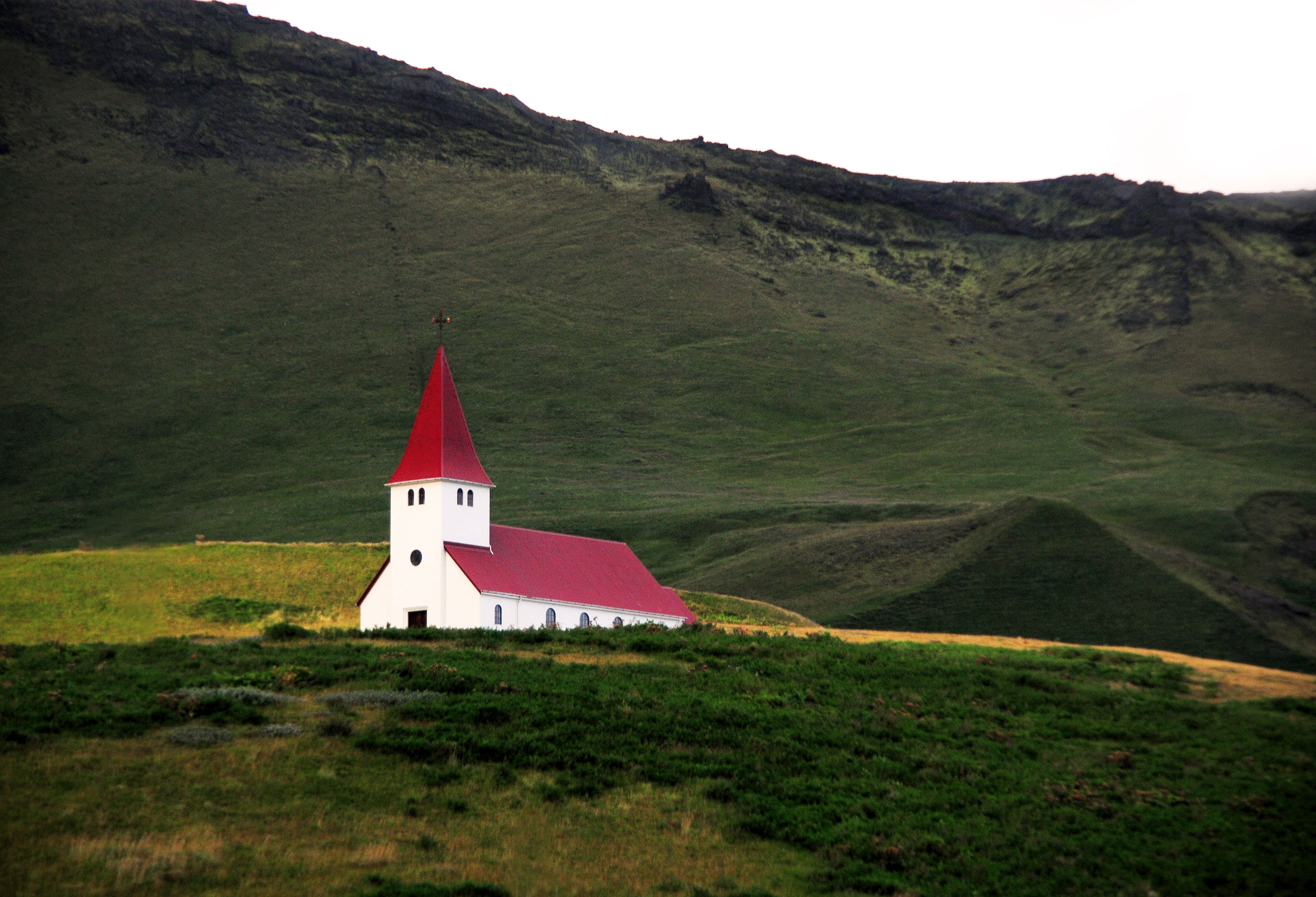 A beautiful church glows on the hillsides of Iceland