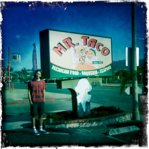 Randy stands beside the Mr. Taco sign in San Marcos, California.