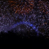 Fireworks exploding over the London Eye ferris wheel in London, England on New Year's Eve.