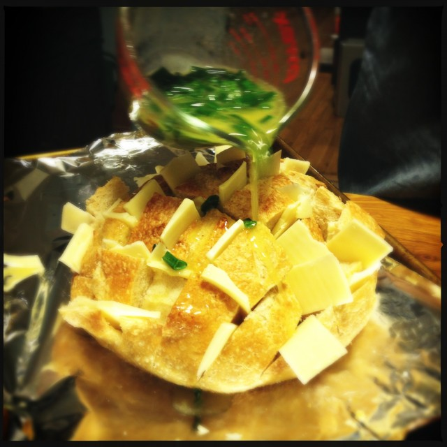 Green onions being poured over a sourdough bread.