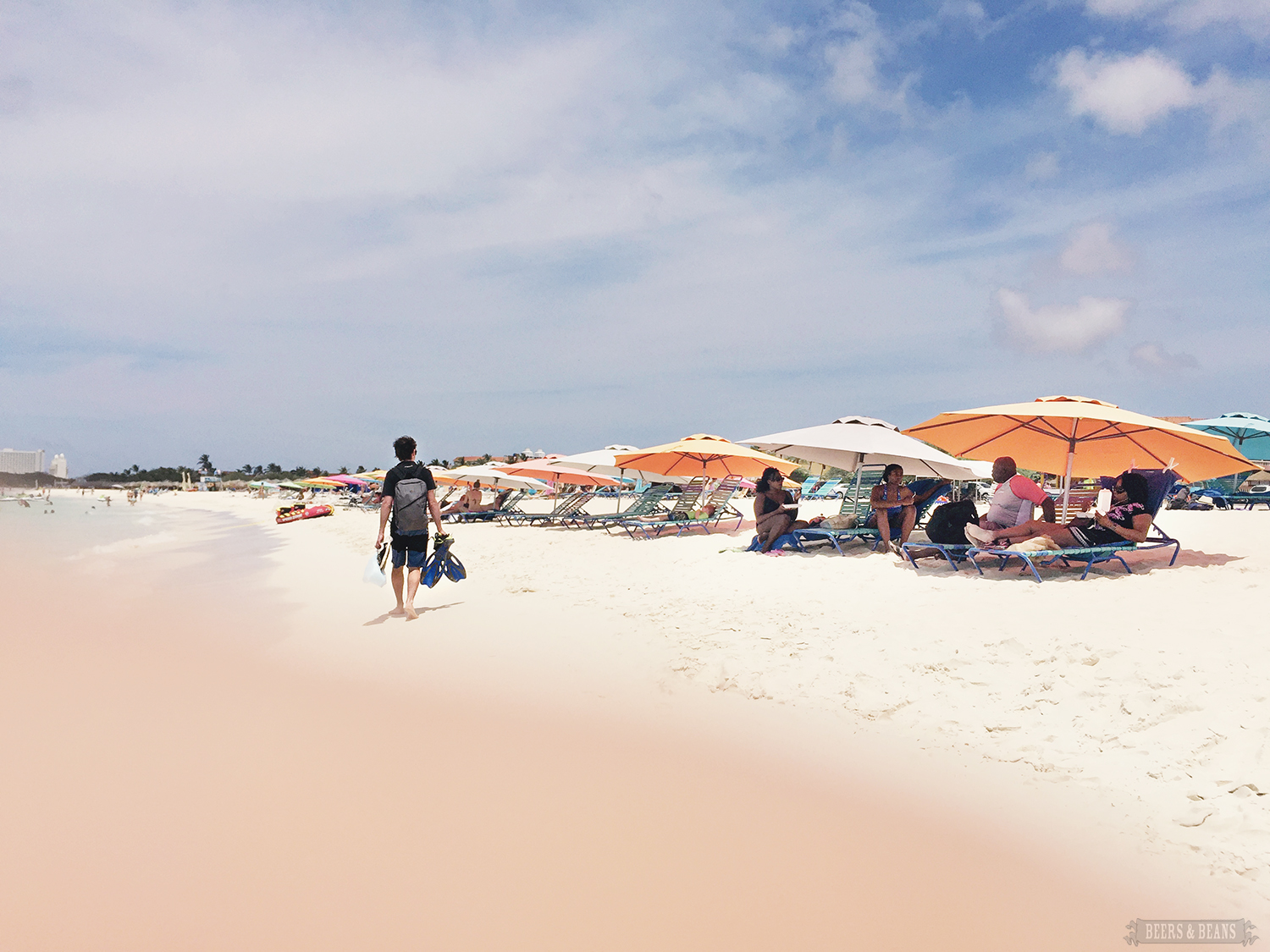 On an Aruba beach, journalist Randy Kalp walks on powder sand past beachgoers under colorful umbrellas.
