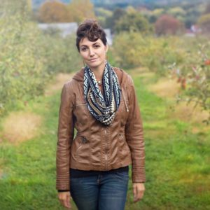 A young traveler wearing a Speakeasy Secret Pocket Travel Scarf while apple picking in New England.