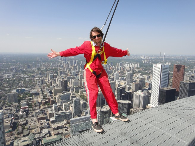 A young man stands on a ledge above Toronto on the Edge Walk.