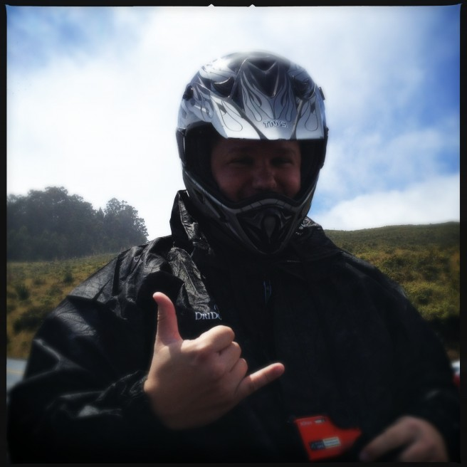 A bike rider throws up a shaka before riding down a Maui volcano.