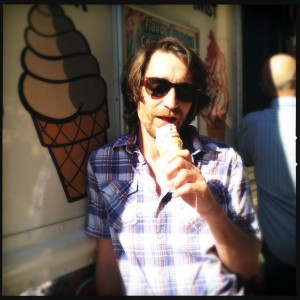 A man is eating an ice cream cone in Toronto.