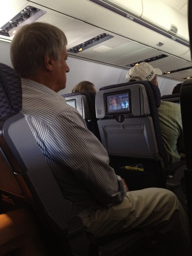 A passenger on a United Airlines Flight with his armrest up.