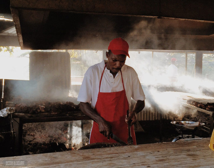 An employee at the Pork Pit barbecue stand in Montego Bay, Jamaica prepares a jerk chicken plate with smoke swirling in the air.