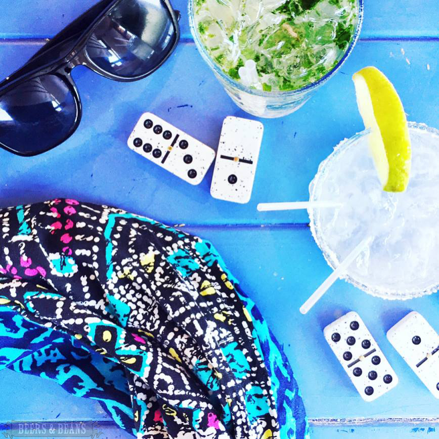 Dominos and a gin and tonic with sunglasses and a hidden pocket travel scarf in Dominican Republic.
