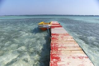 A red pier leads out into the clear, blue Aruba waters.
