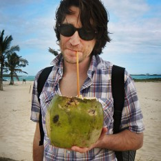 A traveler holding out a coconut rum drink in the Galapagos Islands called the Coco Loco.