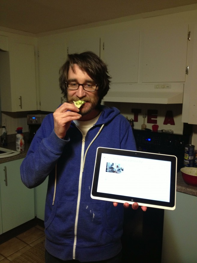A young man tries out Super Bowl Recipe, Avocado dip, while holding his intel tablet, which he used as a cook book.
